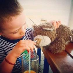 طفل يحاول تقديم الشراب لدميته